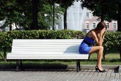 Mujer triste que se sienta en un banco de parque Imagenes de archivo