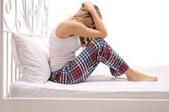 Mujer triste que se sienta en una cama con su cabeza abajo Imagen de archivo libre de regalías