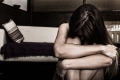 Mujer triste que se sienta solamente en un cuarto vacío al lado de la cama Violencia en el hogar Imagen de archivo libre de regalías