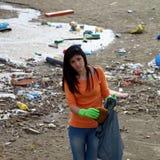 Mujer triste que sostiene el bolso de descarga en la playa sucia Foto de archivo libre de regalías