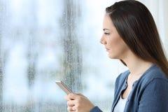 Mujer triste que sostiene el teléfono y que mira a través de una ventana Imágenes de archivo libres de regalías
