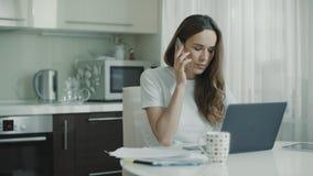 Mujer triste que usa el lugar de trabajo del teléfono en casa Mujer del trastorno que habla el teléfono móvil almacen de video