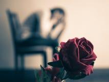 Mujer triste retra que se sienta y que llora con la rosa del rojo en foco Fotografía de archivo