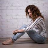 Mujer triste sola que se sienta en el piso sobre la pared de ladrillo Imagen de archivo
