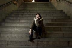 Mujer triste solamente en la depresión sufridora de la escalera del subterráneo de la calle que mira que parece enfermo y desampa foto de archivo