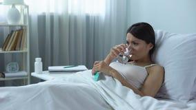 Mujer triste y frustrada que toma las píldoras fuertes que mienten en la cama, curso de la quimioterapia almacen de video