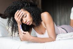 Mujer triste y preocupante con una prueba de embarazo en cama Fotografía de archivo