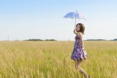 Mujer triste y sola hermosa con el paraguas que camina en el trigo fi Fotografía de archivo