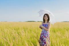 Mujer triste y sola hermosa con el paraguas que camina en el trigo fi Foto de archivo libre de regalías