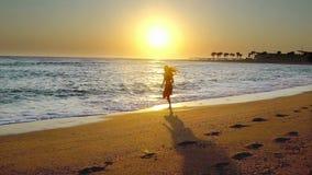 Mujer trotando en el mar de playa y amanecer almacen de video