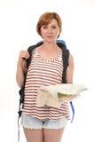 Mujer turística americana atractiva joven con el pelo rojo que sostiene la mochila del backpacker del mapa de la ciudad que lleva Imagenes de archivo