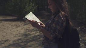 Mujer turística atractiva joven con la mochila que mira a su mapa y que levanta encima de ojos que comprueba con el terreno local almacen de metraje de vídeo
