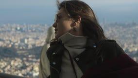 Mujer turística atractiva joven en gafas de sol con la estatua y la ciudad en fondo almacen de video
