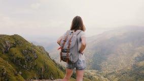 Mujer turística caucásica joven con la mochila y cámara que disfrutan de momentos felices en el Mountain View escénico épico en S metrajes