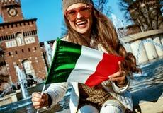 Mujer turística cerca del castillo de Sforza en Milán, Italia que muestra la bandera foto de archivo