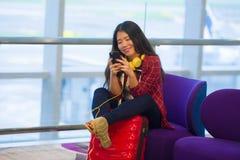 Mujer turística coreana feliz y bastante asiática joven que se sienta en el vuelo que espera de la puerta de embarque de la salid fotos de archivo libres de regalías