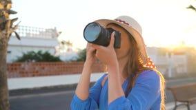 Mujer turística del fotógrafo que toma las fotos con la cámara en un paisaje tropical hermoso en la puesta del sol metrajes
