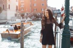Mujer turística del viaje en el embarcadero contra hermosa vista en el chanal veneciano en Venecia, Italia fotografía de archivo libre de regalías