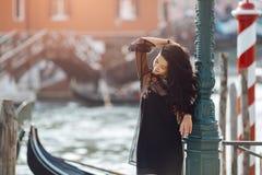 Mujer turística del viaje en el embarcadero contra hermosa vista en el chanal veneciano en Venecia, Italia fotos de archivo