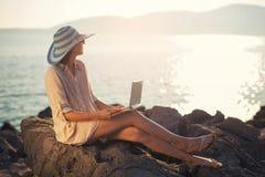 Mujer turística el días de fiesta que goza en línea con un ordenador portátil en la playa Imagen de archivo