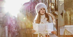 Mujer turística elegante en Venecia, Italia en invierno con el mapa fotos de archivo libres de regalías