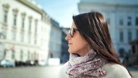 Mujer turística elegante sonriente del primer medio en gafas de sol que bebe el café que disfruta de caminar al aire libre almacen de metraje de vídeo