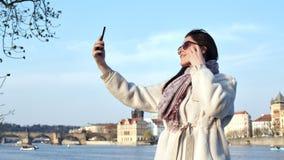 Mujer turística elegante sonriente del tiro medio que toma el selfie usando smartphone en el terraplén en la puesta del sol almacen de video