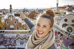 Mujer turística en el parque de Guell que toma la foto con el teléfono móvil Fotografía de archivo libre de regalías