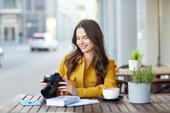 Mujer turística feliz con la cámara en el café de la ciudad Fotos de archivo libres de regalías