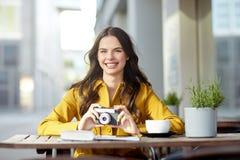 Mujer turística feliz con la cámara en el café de la ciudad Fotografía de archivo libre de regalías