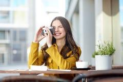 Mujer turística feliz con la cámara en el café de la ciudad Foto de archivo libre de regalías