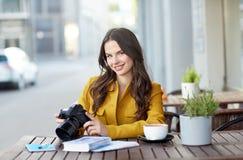 Mujer turística feliz con la cámara en el café de la ciudad Imagenes de archivo