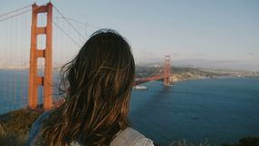 Mujer turística feliz de la visión trasera con el pelo que sopla en el viento que mira paisaje épico de la puesta del sol en puen almacen de metraje de vídeo