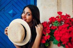 Mujer turística feliz que sonríe contra fondo azul por las flores rojas al aire libre Vacaciones de verano Imágenes de archivo libres de regalías
