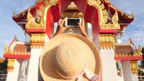 Mujer turística joven atractiva en el vestido blanco y Straw Hat Taking Photo grande con el teléfono móvil del templo budista tai metrajes
