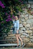 Mujer turística joven atractiva que visita una calle pebbled con el monumento texturizado de la pared de piedra, dando vuelta par Imagen de archivo
