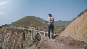 Mujer turística joven con la mochila que mira paisaje épico en el punto en Big Sur soleado, California del vista del puente del b almacen de metraje de vídeo