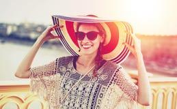 Mujer turística joven feliz que sostiene el sombrero Imágenes de archivo libres de regalías