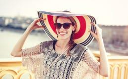 Mujer turística joven feliz que sostiene el sombrero Fotos de archivo libres de regalías