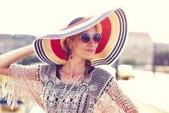 Mujer turística joven feliz que sostiene el sombrero al aire libre foto de archivo