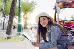 Mujer turística joven hermosa que toma un resto en el taxi del tuk del tuk y que encuentra una cierta atracción turística en mapa fotografía de archivo libre de regalías