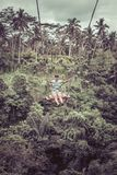 Mujer turística joven que balancea en el acantilado en la selva tropical de la selva de una isla tropical de Bali, Indonesia Fotos de archivo libres de regalías