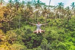 Mujer turística joven que balancea en el acantilado en la selva tropical de la selva de una isla tropical de Bali, Indonesia Foto de archivo