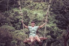 Mujer turística joven que balancea en el acantilado en la selva tropical de la selva de una isla tropical de Bali, Indonesia Fotografía de archivo libre de regalías