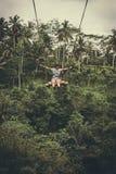 Mujer turística joven que balancea en el acantilado en la selva tropical de la selva de una isla tropical de Bali, Indonesia Imagenes de archivo