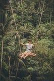 Mujer turística joven que balancea en el acantilado en la selva tropical de la selva de una isla tropical de Bali, Indonesia Foto de archivo libre de regalías