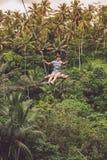 Mujer turística joven que balancea en el acantilado en la selva tropical de la selva de una isla tropical de Bali, Indonesia Fotos de archivo