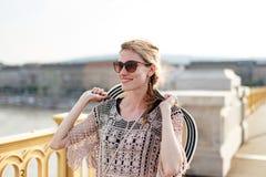 Mujer turística joven que sostiene el sombrero mientras que camina en el puente Foto de archivo