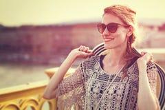 Mujer turística joven que sostiene el sombrero mientras que camina en el puente Fotos de archivo libres de regalías