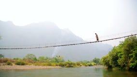 Mujer turística que cruza puente colgante de bambú peligroso, Laos metrajes